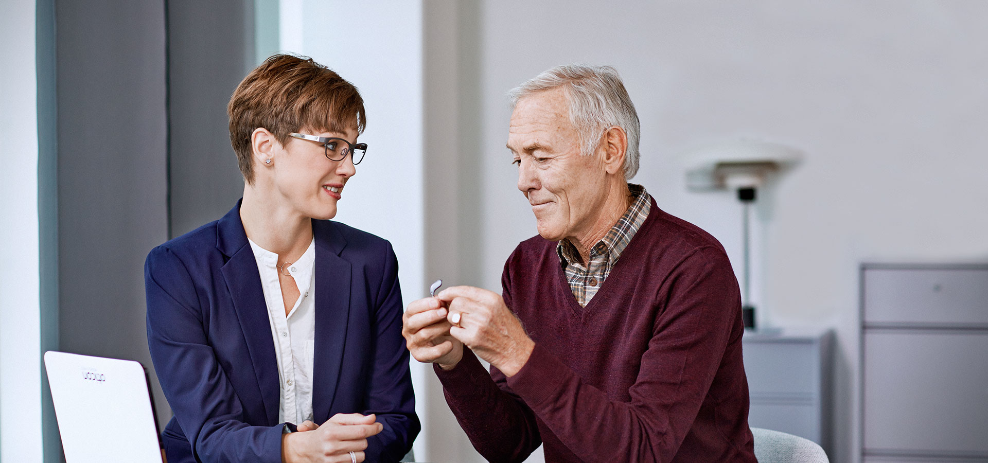 woman helping man with hearing aid