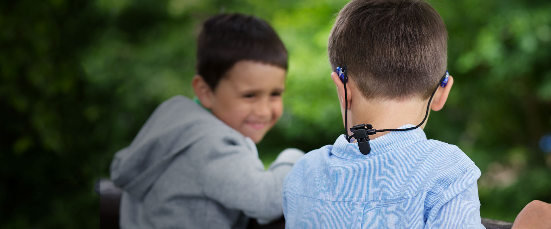 Boy with retention cord for hearing aids