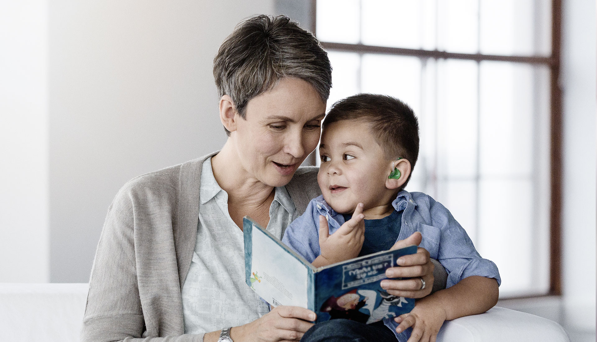 woman reading a book to a young boy